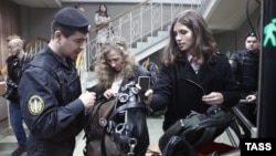 Pussy Riot's Maria Alyokhina (center) and Nadezhda Tolokonnikova (right) enter a court building in Moscow on January 9.