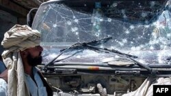 FILE: An Afghan man looks at a vehicle damaged by a suicide attack in Gardez.