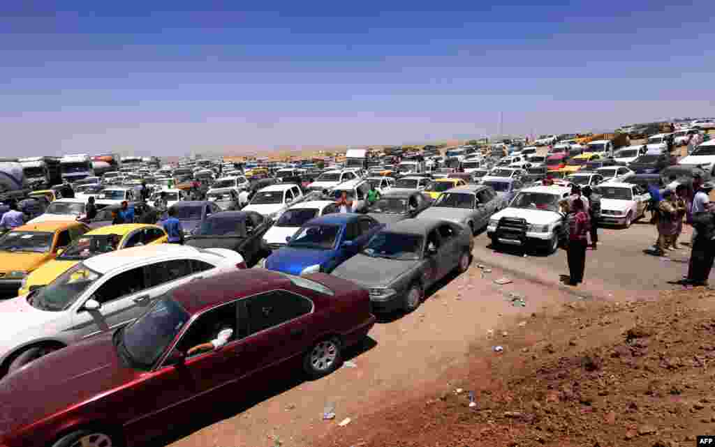 Iraqis fleeing violence in Nineveh Province wait in their vehicles at a Kurdish checkpoint in Aski Kalak, 40 kilometers west of Irbil, the capital of the northern autonomous Kurdish region, on June 10. (AFP/Safin Hamed)