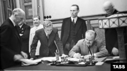Soviet Foreign Minister Vyacheslav Molotov signs the nonaggression pact between Germany and the Soviet Union in Moscow on August 23, 1939, as Soviet dictator Josef Stalin looks on (left rear).