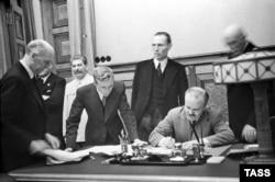 Міністр закордонних справ СРСР В'ячеслав Молотов (праворуч, сидить) підписує пакт Молотова-Ріббентропа. Третій ліворуч – голова уряду СРСР Йосиф Сталін. Москва, 23 серпня 1939 року
