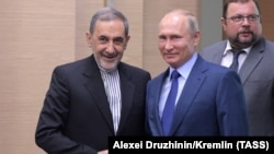 Ali Akbar Velayati, senior adviser to the Supreme Leader of Iran and Russia's President Vladimir Putin (L-R front) shake hands during a meeting at Novo-Ogaryovo residence. July 12, 2018