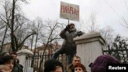 """Участник протеста на заборе держит плакат """"Майдан"""" перед зданием суда. Москва, 24 февраля 2014 года."""
