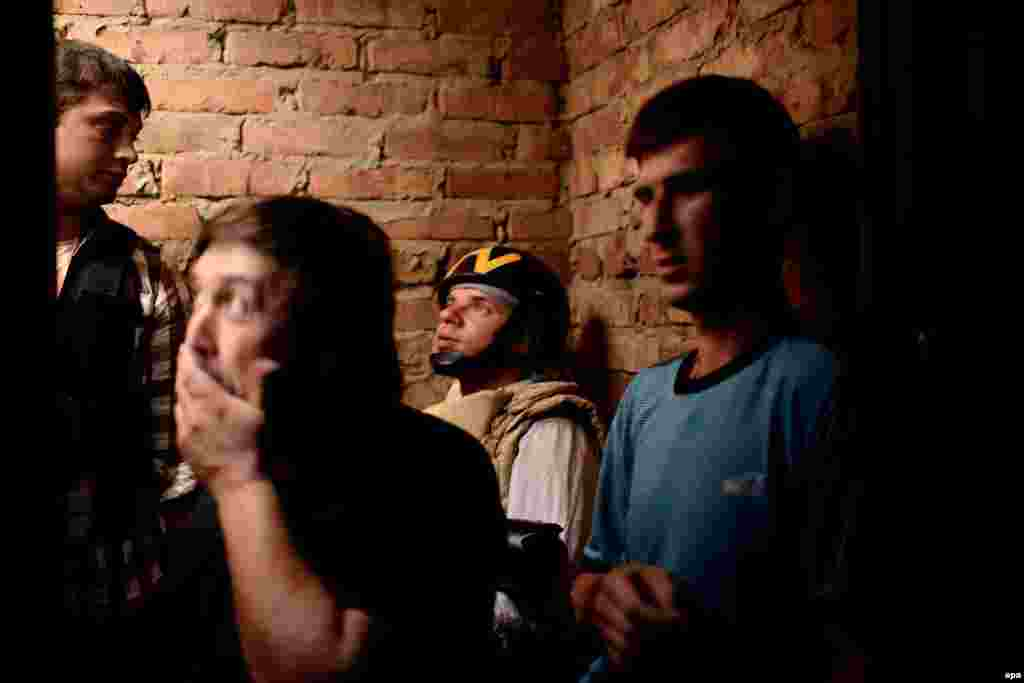 A journalist of TV Belsat (2nd right) and locals stand in a basement during a mortar barrage in the eastern Ukrainian village of Semyonovka, outside Slovyansk, on May 26. (epa/Jakub Kaminski)