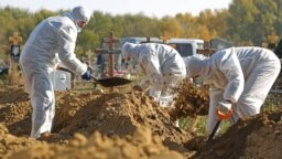 Cemetery workers wearing protective gear bury people who died of COVID-19 in Omsk.