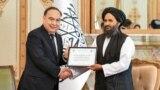 Казакстан президентинин атайын өкүлү Ержан Казыханов (солдо) Абдул Гани Барадарга беш миң тонна гуманитардык жардам сертификатын тапшырды.
