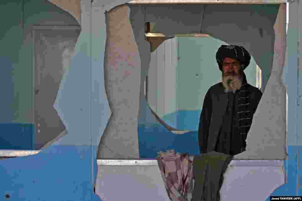 Учитель стоит в обстрелянной пулями школе в деревне Бабро в афганском районе Аргандаб