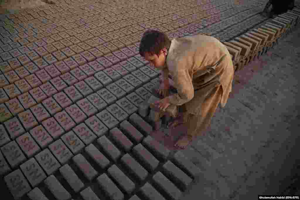 Një djalë afgan teksa punon në një furrë të tullave në provincën Nangarhar.