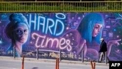 """Прохожий в защитной маске на фоне уличного граффити с надписью """"Тяжелые времена"""". Приштина, Косово"""