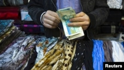 A shopkeeper counts bank notes at a bazaar in Tehran.