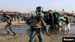 Afghan policemen inspect the site of a bomb explosion in Jalalabad on December 17.