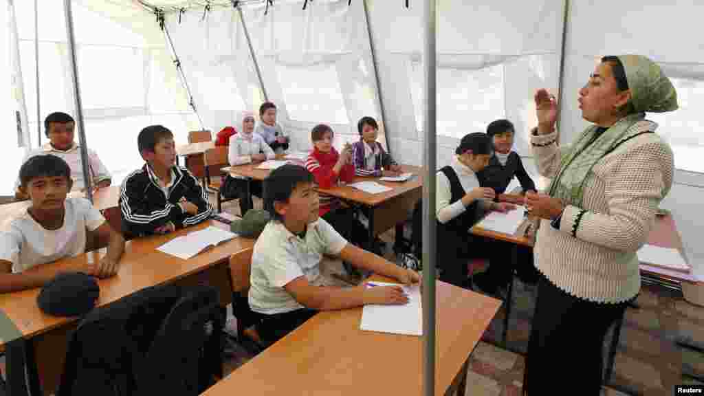 Kyrgyz children listen to their teacher during a lesson at a local school in a tent in the city of Osh.