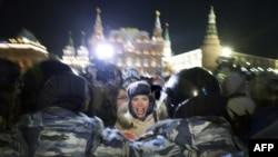 Қоғам белсендісі Алексей Навальныйды соттауға қарсы наразылық акциясына қатысушыны полиция ұстап әкетіп барады. Мәскеу, 30 желтоқсан 2014 жыл