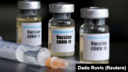 """Small bottles labbeled with a """"Vaccine COVID-19"""" sticker and a medical syringe = generic"""