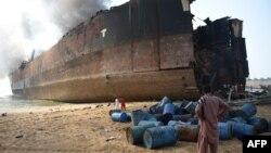 Човек од Пакистан гледа во бродот еден ден по експлозијата.