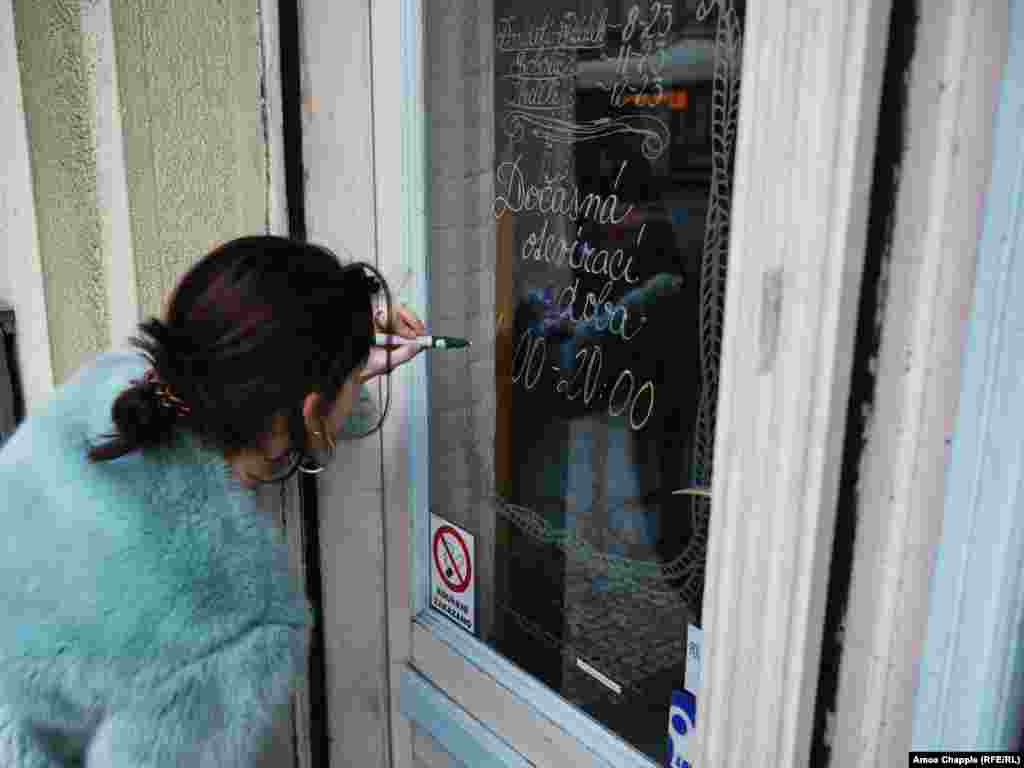 A waitress writes the new opening hours of her cafe in Nusle. From March 13, restaurants and bars were required to close by 8 p.m. On March 14, the Czech government declared such businesses must shut down completely for ten days.