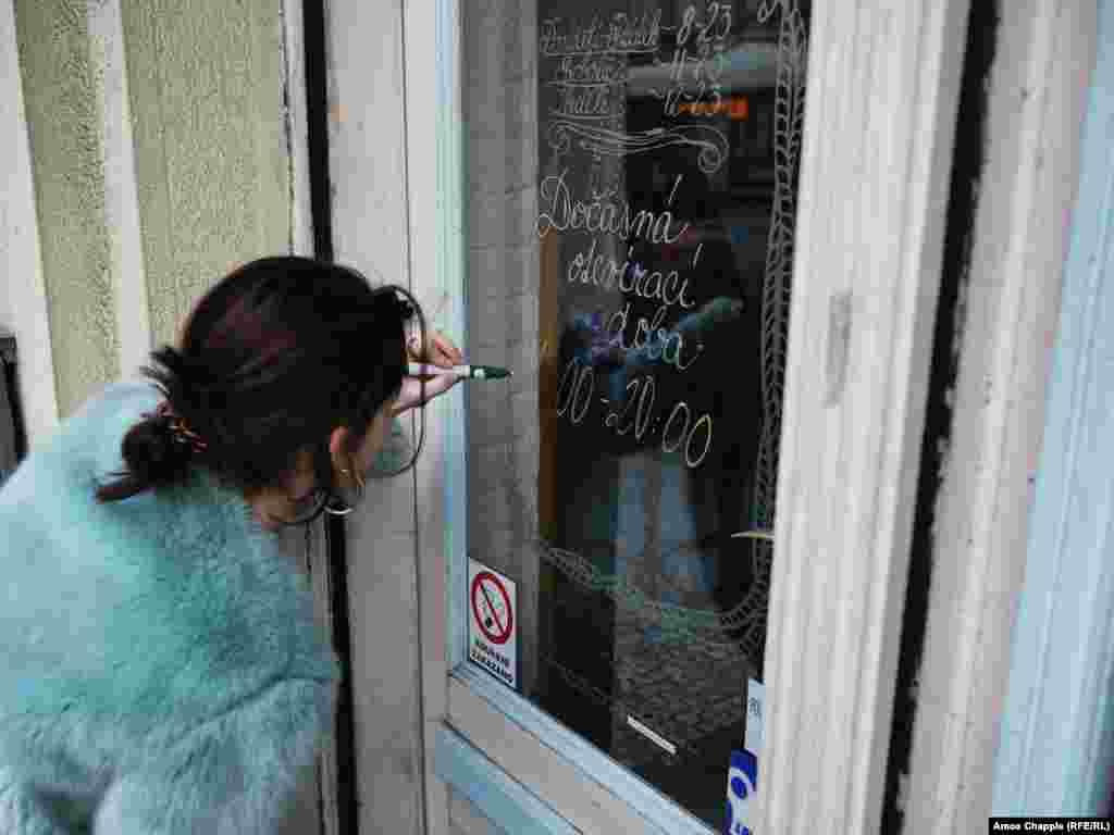 ოფიციანტი ქალი კაფეს კარებზე წერს ახალ სამუშაო საათებს. 13 მარტიდან რესტორნებსა და ბარებს 20:00 საათამდე უნდა ემუშავათ, მაგრამ 14 მარტს ჩეხეთის მთავრობამ 10 დღის განმავლობაში საერთოდ აუკრძალა მუშაობა ასეთ დაწესებულებებს.