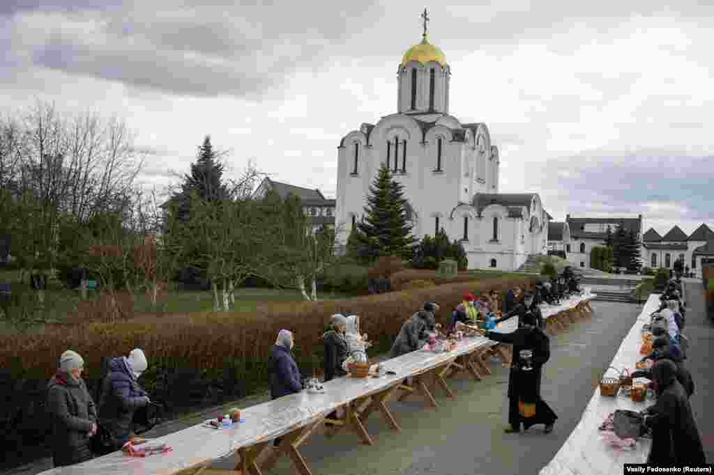 "An Orthodox priest sprinkles holy water on believers and their ""paskha"" cakes and eggs on the eve of Orthodox Easter in Minsk on April 18."