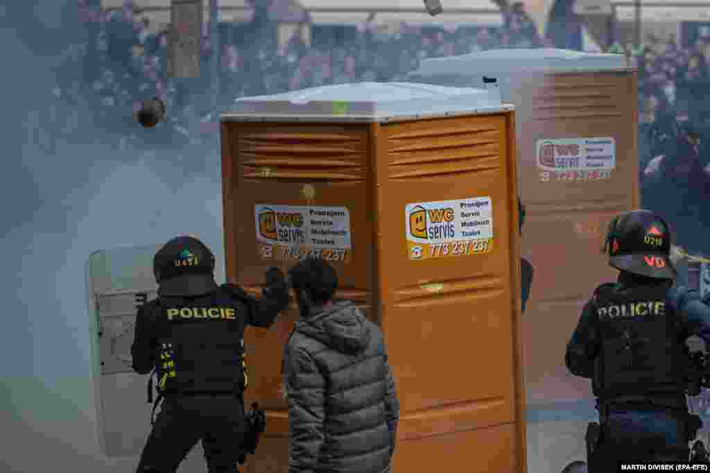 Riot police face-off with protesters as hundreds of demonstrators, mostly hooligans, protest against the Czech government's new measures in connection with the COVID-19 pandemic caused by the SARS-CoV-2 coronavirus, at the Old Town Square in Prague, October 18, 2020.