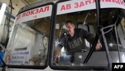 Водій розглядає осколкові отвори на лобовому склі автобуса, який був пошкоджений недалеко від Донецького аеропорту. Листопад 2014 року