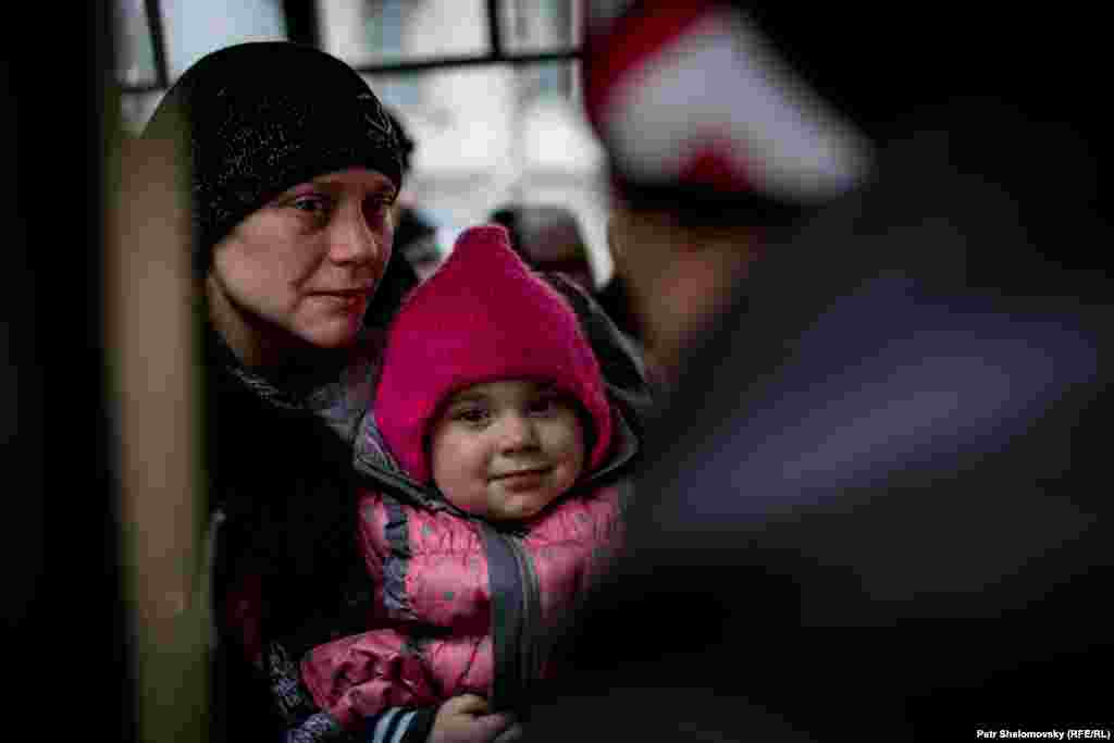 Эвакуируемые жители вместе с детьми в салоне автобуса, выезжающего из Дебальцева.