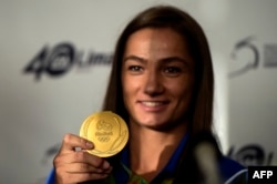 Kosovar judoka Majlinda Kelmendi shows her gold medal to fans during a welcoming ceremony in Pristina in August 2016.