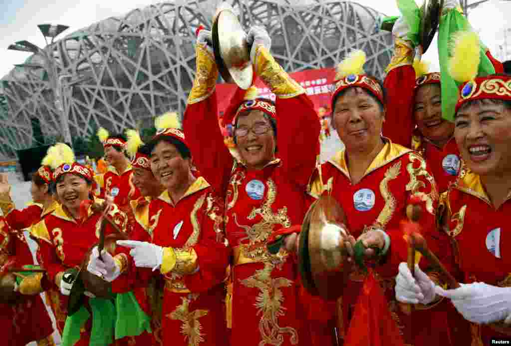Meanwhile, performers in Beijing cheer ahead of the International Olympic Committee's announcement that the Chinese capital has been chosen for the 2022 Winter Olympics on July 31. (Reuters/​Damir Sagolj)
