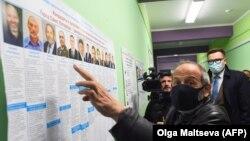 Борис Вишневски от опозиционната партия Яблоко показва таблото в избирателната си секция в Санкт-Петербург. На него се виждат трима кандидати с неговото име, двама от които са сменили и външността си, за да приличат на него.