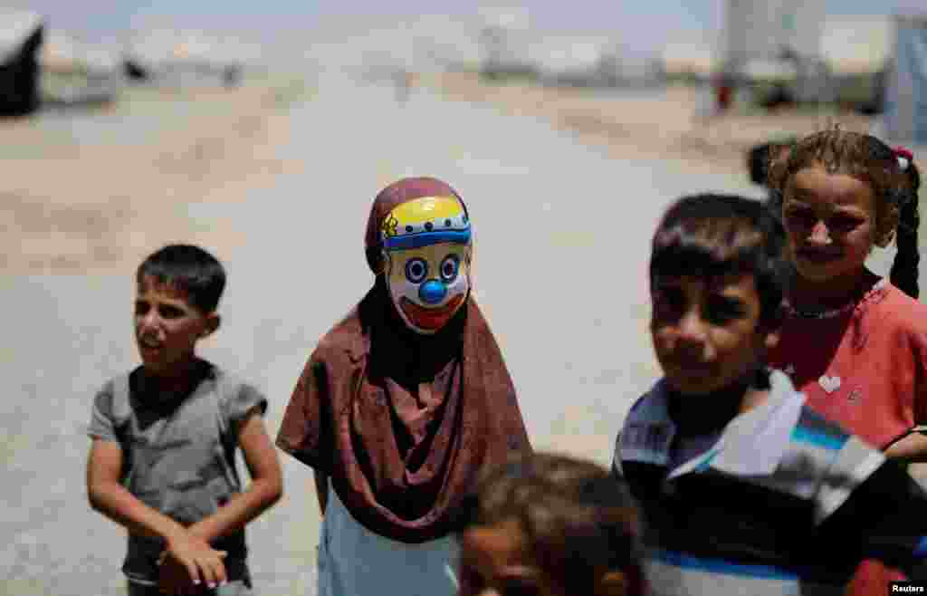 A displaced Iraqi girl wears a clown mask at the Hasansham camp in Al-Khazer, east of Mosul. (Reuters/Alkis Konstantinidis)