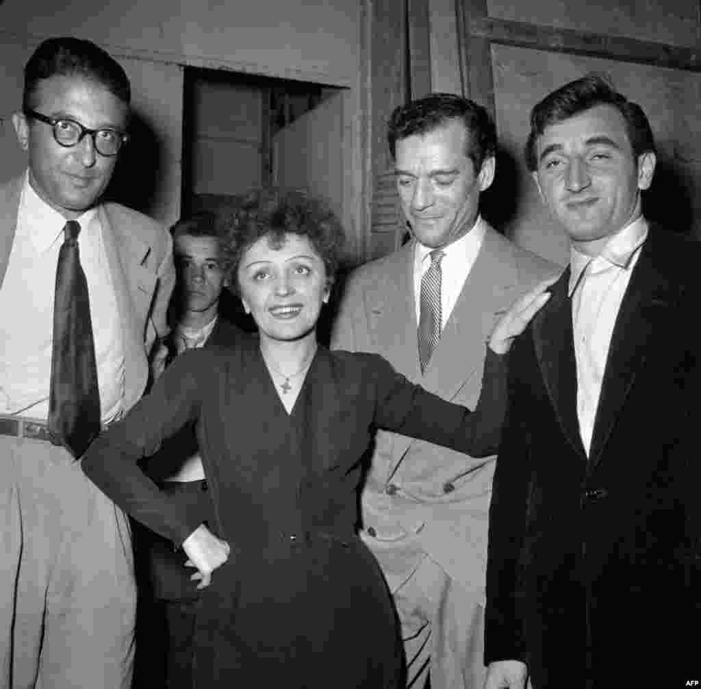 Piaf with French composer Michel Emer, American actor Eddie Constantine, and French singer of Armenian origin Charles Aznavour (left to right). (undated)