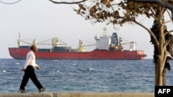 "A man walks on the seafront promenade in Limassol as the Russian-owned cargo ship ""Monchegorsk"" is docked offshore. (file photo)"