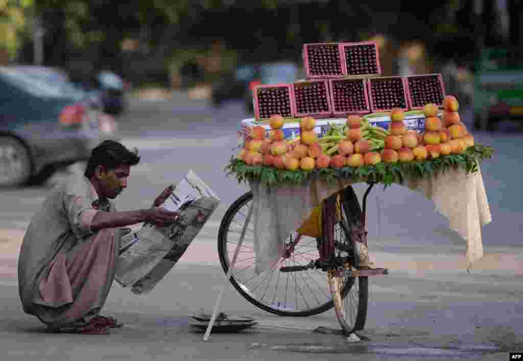 A Pakistani fruit vendor reads a newspaper as he waits for customers on a street in Islamabad. (AFP/Aamir Qureshi)