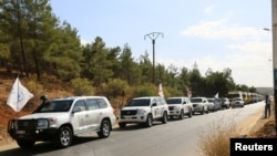 A convoy carrying food and humanitarian supplies waits as they head to deliver aid to Syrian besieged towns, near Damascus, in September.