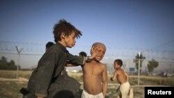 هیلمند: په افغانستان کې ماشومان د لوبې پر مهال. د یوه رپورټ تر مخې هر کال په زرګونه افغانان چې په کې ماشومان هم وي د غریبۍ له کبله نورو هېوادونو ته ځي. اسټرالیا غواړي کډوال افغان ماشومان خپل هېواد ته ستانه کړي. دا انځور د ۲۰۱۱ز کال د جون د ۲۲مې دی.