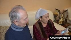 Кудайберген Айтбаев и Миуа Низамудинова смотрят в телефоне сообщение о выступлении их внука Димаша Кудайбергена в Китае.