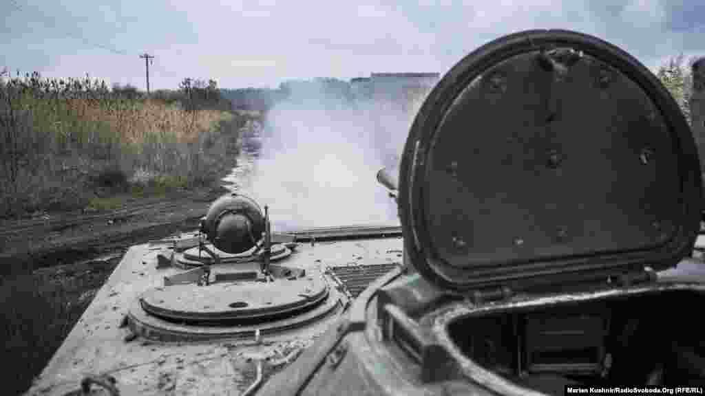 Военный выполняет выстрел по условной мишени - танку в поле. Цель была поражена.