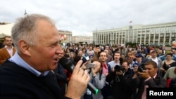 Belarusian opposition leader Mikalay Statkevich delivers a speech during a protest rally on Belarusian Independence Day in Minsk on July 3.