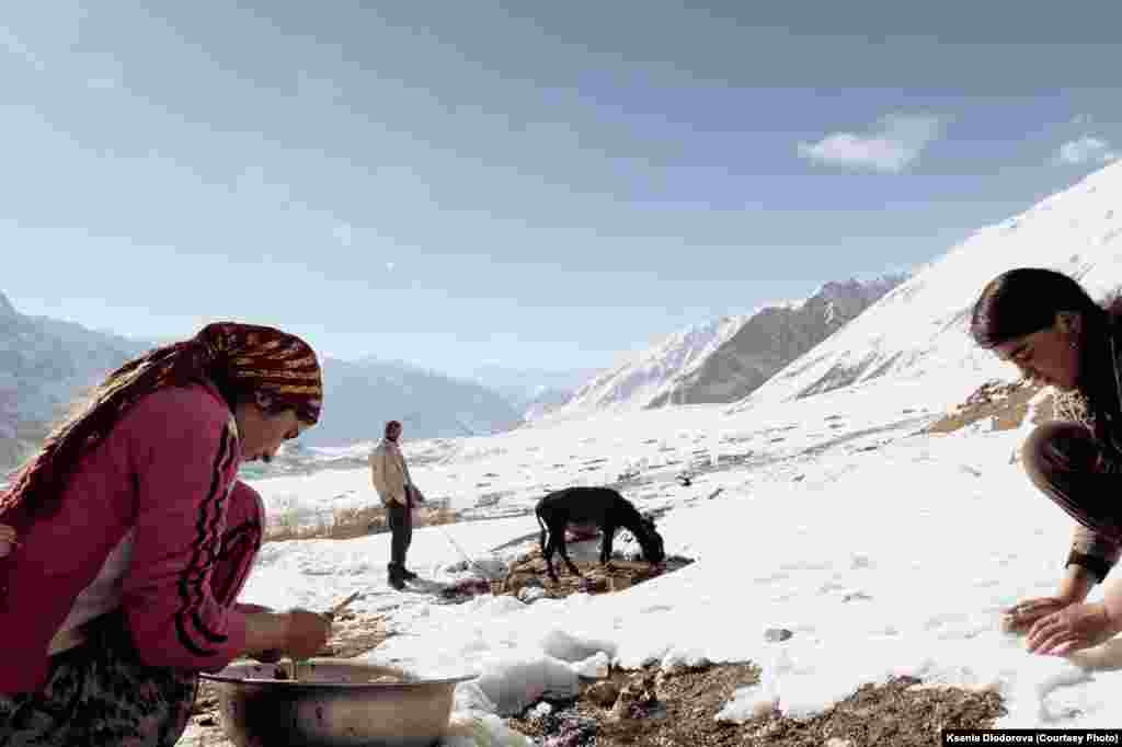Young women wash the entrails of a slaughtered sheep in a river in the Pamir mountains.