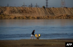 An Afghan man transports containers of water in a wheelbarrow alongside the Amu River on the border of Afghanistan and Uzbekistan.