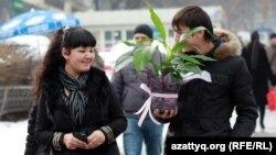 Парень с цветами и девушка идут по улице Алматы. 7 марта 2012 года.