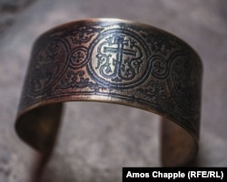 A bracelet featuring the Orthodox Christian cross, cut from a spent artillery shell