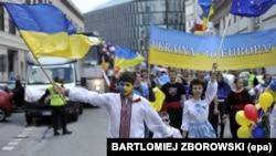 Молодые люди размахивают украинскими флагами и несут знамя, присоединяясь к Параду Шумана в Варшаве, 10 мая 2014 г.