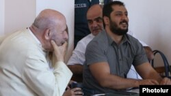 Armenia - Father Anton Totonjian (L) and Artur Vartanian (R) stand trial on coup charges in Yerevan, 28Jul2017.