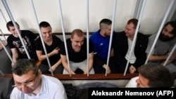 Ukrainian sailors sit inside a defendants' cage at a court hearing in Moscow on July 17.