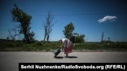На цьому фото не Людмила – це інша така сама літня жінка з металевим возиком дістається через лінію фронту біля Станиці Луганської