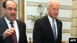 Iraqi Prime Minister Nuri al-Maliki (left) walks with U.S. Vice President Joe Biden in Baghdad on January 13.