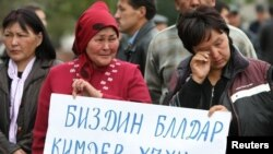 Friends and relatives of people killed during the April uprising that drove the former president from power rally against the policies of the Ata-Jurt party in Bishkek.