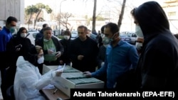 An Iranian lab official registers people for coronavirus testing outside a lab in Tehran on March 9.