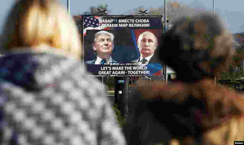 A billboard showing pictures of U.S. President-elect Donald Trump and Russian President Vladimir Putin is seen through pedestrians in Danilovgrad, Montenegro. (Reuters/Stevo Vasiljevic)