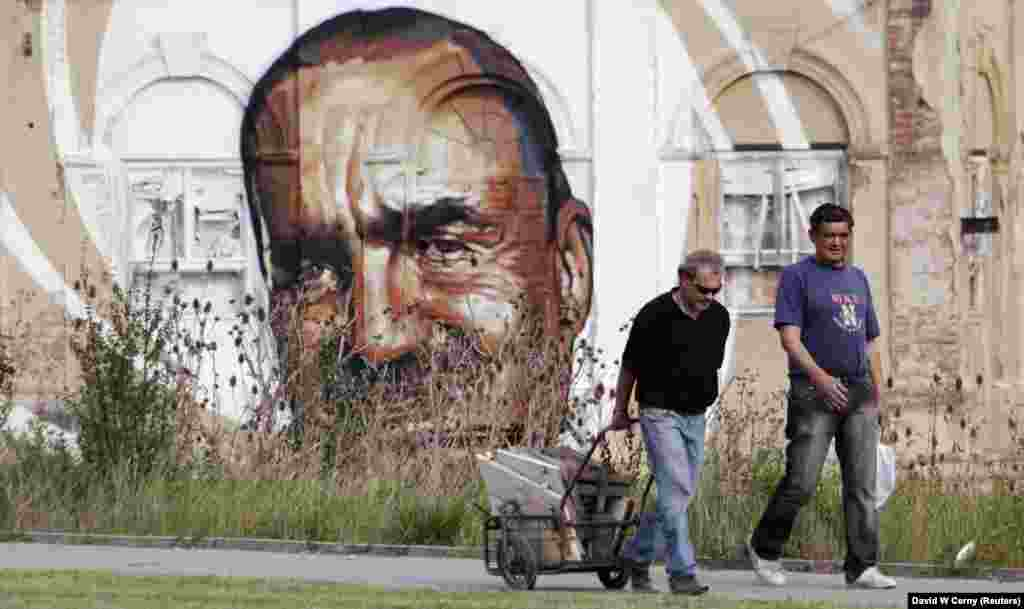 A man pulls a cart full of scrap materials past a mural depicting TOP09 party chairman Karel Schwarzenberg that has been painted on an abandoned building in Prague.